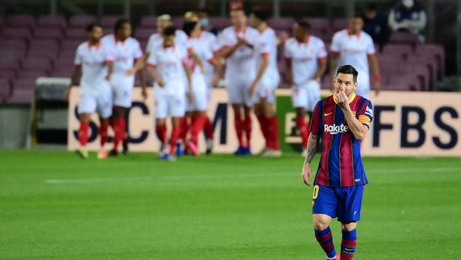 Lionel Messi tampak lemas saat Sevilla sukses cetak gol ke gawang Barcelona pada laga lanjutan Liga Spanyol 2020/2021, Senin (5/10/2020) dini hari WIB. (LLUIS GENE / AFP)
