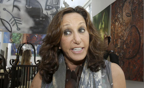 Fashion designer Donna Karan talks to a reporter during her visit to Little Haiti at the Discover Haiti Exhibition in Miami, Friday, May 17, 2013. Karan is among the designers and celebrities who have advocated for Haitian artisans since a catastrophic earthquake shook the Caribbean country in 2010. (AP Photo/Alan Diaz)