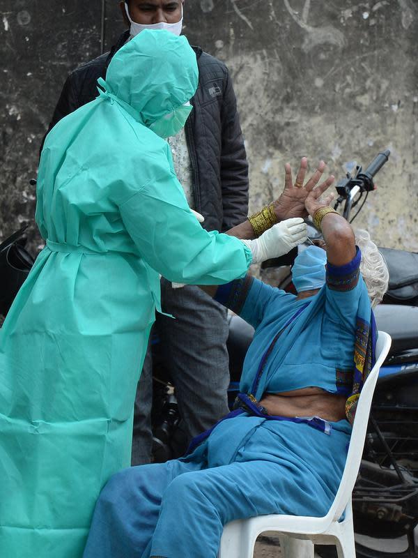 Seorang petugas kesehatan mengumpulkan sampel usap dari seorang wanita untuk menguji virus Covid-19 di daerah kumuh di Hyderabad (23/9/2020). Infeksi virus corona di India kembali melonjak pada Rabu (23/9) setelah sehari sebelumnya menyentuh angka terendah dalam hampir sebulan. (AFP/Noah Seelam)