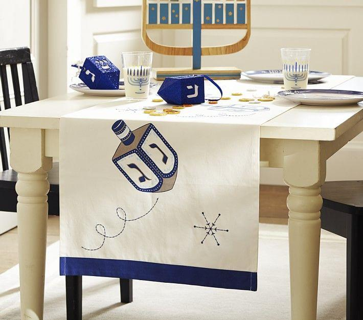 "<p><strong>pottery barn</strong></p><p>potterybarnkids.com</p><p><strong>$18.99</strong></p><p><a href=""https://go.redirectingat.com?id=74968X1596630&url=https%3A%2F%2Fwww.potterybarnkids.com%2Fproducts%2Fhanukkah-runner%2F%3Fsku%3D2205474%26cm_ven%3DPLA%26cm_ite%3D2205474%26cm_cat%3DGoogle%26cm_pla%3DLocal%26gclid%3DCjwKCAjw-5v7BRAmEiwAJ3DpuLmb2nvrxHDIYXZL5dqaTqUTvkrtP86A6_RdofqLmZRN8GPahrqPqRoCIzEQAvD_BwE&sref=https%3A%2F%2Fwww.womansday.com%2Fhome%2Fdecorating%2Fg34087622%2Fhanukkah-decorations%2F"" target=""_blank"">Shop Now</a></p><p>This dreidel-embroidered runner will make the perfect start to your Hanukkah tablescape. It features elegant stitching and is also machine washable, for easy cleaning and reuse year after year.</p>"