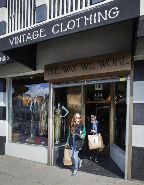 "In this photo taken Thursday, Feb. 21, 2013, interior and fashion designer, Kelly Wearstler, left, is helped by consultant Sarah Bergman, after shopping for vintage designs ""The Way We Wore,"" a Hollywood high-end vintage store owned by Doris Raymond in the La Brea District of Los Angeles. Raymond's vintage clothing and accessories store is featured in the reality TV series, ""L.A. Frock Stars,"" which debuts March 7, 2013 on the Smithsonian Channel. (AP Photo/Damian Dovarganes)"
