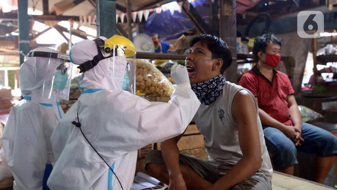 Petugas medis Kecamatan Gambir melakukan tes swab terhadap pedagang Pasar Thomas, Jakarta, Rabu (17/6/2020). Tes swab dilakukan untuk memutus rantai penularan virus corona COVID-19. (merdeka.com/Imam Buhori)