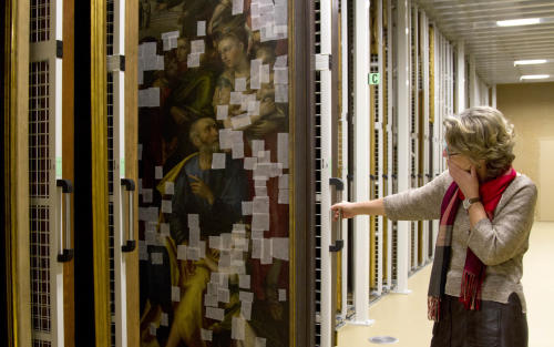 "Press and communications officer Veronique Van Passel pulls out a painting which is patched to prevent flaking paint as it is stored at the Antwerp Royal Museum of Fine Arts in Antwerp, Belgium on Thursday, April 4, 2013. Just as the famous Amsterdam Rijksmuseum in neighbouring Netherlands has returned ""The Night Watch"" of its most famous painter, Rembrandt van Rijn, back in the main building after a ten-year renovation, Antwerp is hiding five oversized Rubens paintings in a special depot to protect them against the rough and tumble of four more years of works. (AP Photo/Virginia Mayo)"