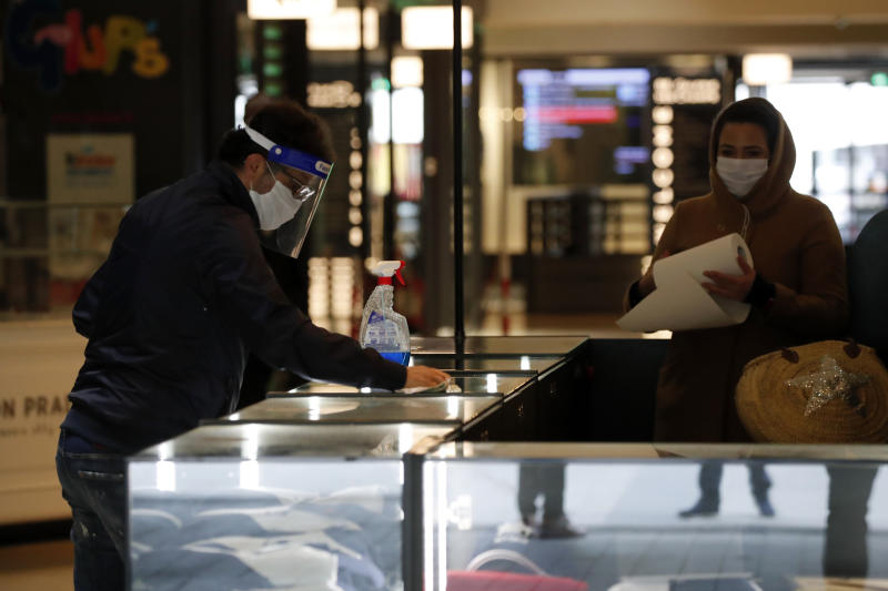 Employees clean their desk in a shopping mall Monday, May 11, 2020 in Paris. The French began leaving their homes and apartments for the first time in two months without permission slips as the country cautiously lifted its lockdown. Clothing stores, coiffures and other businesses large and small were reopening on Monday _ with strict precautions to keep the coronavirus at bay. (AP Photo/Francois Mori)