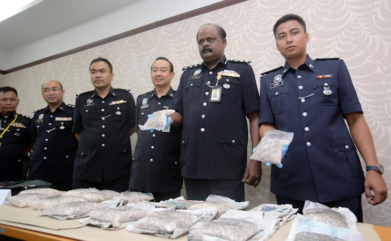 State Narcotics Criminal Investigation Department chief, ACP VR Ravi Chandran (2nd right) poses for pictures with the heroin seizure at the state police headquarters in Ipoh April 19, 2019. — Picture by Farhan Najib