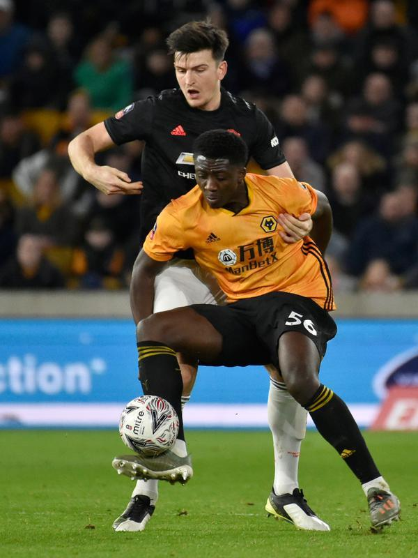 Pemain Wolverhampton Wanderers, Benny Ashley-Seal berebut bola dengan bek Manchester United, Harry Maguire pada babak ketiga Piala FA di Molineux, Sabtu (4/1/2020). Wolverhampton dan MU dipaksa untuk melakukan laga ulangan di Old Trafford usai bermain imbang tanpa gol. (AP/Rui Vieira)