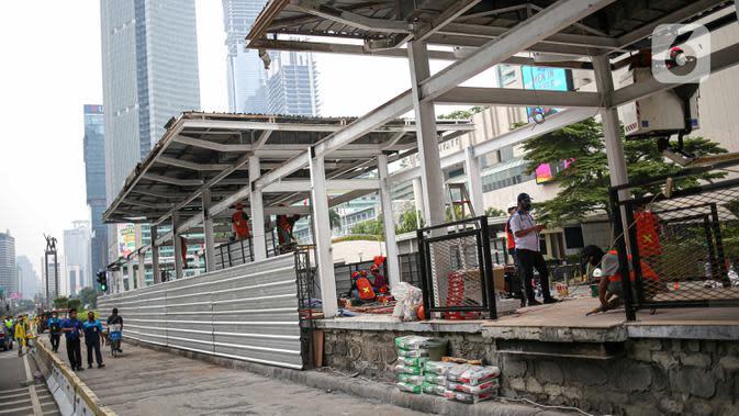 Pekerja menyelesaikan perbaikan Halte Transjakarta yang dibakar pasca aksi unjuk rasa di kawasan Bundara HI, Jakarta, Minggu (11/10/2020). Kerugian 46 halte bus rusak kerugiannya diperkirakan mencapai Rp 65 miliar. Perbaikan selesai diperkirakan 1 hingga 2 bulan. (Liputan6.com/Faizal Fanani)