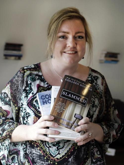 In the photo made Tuesday, Feb. 5, 2013, self publishing author Colleen Hoover posses and holds copies her books in Sulphur Springs, Texas. Hoover's romance novels books have made the New York Times bestseller list. (AP Photo/LM Otero)