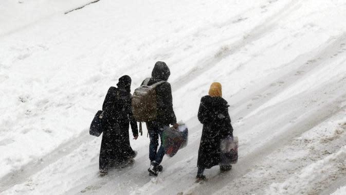 Warga Suriah berjalan di jalan yang tertutup salju di kota Maaret al-Numan, di provinsi utara Idlib, Suriah, pada 21 Desember 2016 (AFP Photo)