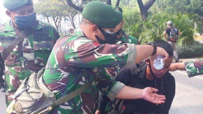 Prajurit TNI menolong anggota Polisi yang terkena gas air mata