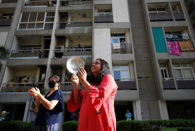 Residents clap and bang utensils to cheer for emergency personnel and sanitation workers who are on the frontlines in the fight against coronavirus, in Ahmedabad