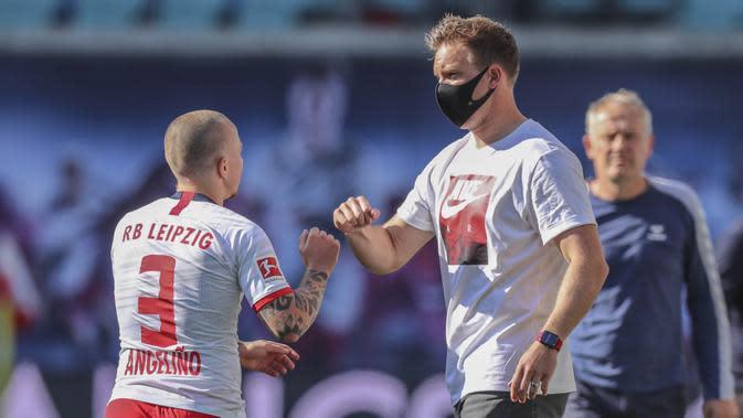 Pelatih RB Leipzig, Julian Nagelsmann, melakukan selebrasi bersama Angelino saat melawan SC Freiburg pada laga Bundesliga di Leipzig, Sabtu (16/5/2020). Pandemi COVID-19 membuat pemain melakukan selebrasi jaga jarak. (AFP/Jan Woitas)