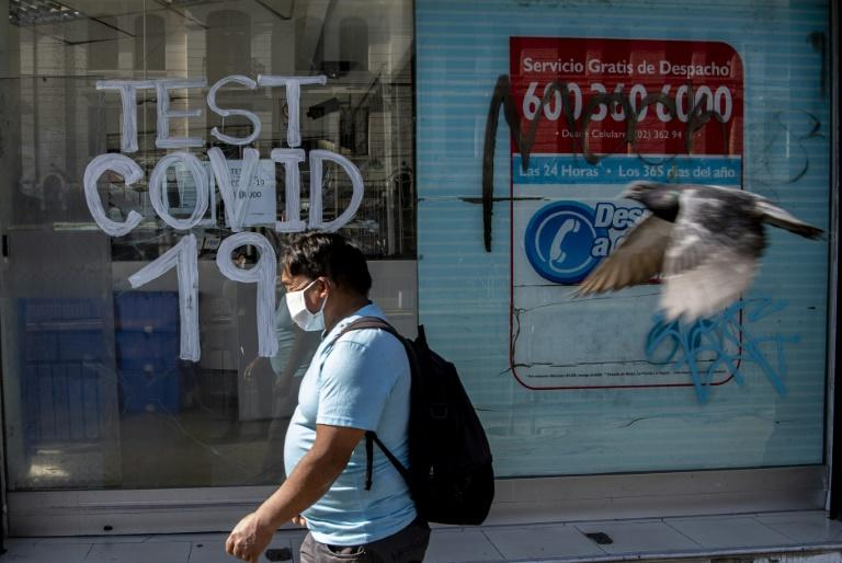A man walks past a pharmacy where COVID-19 tests are conducted in  Santiago, Chile