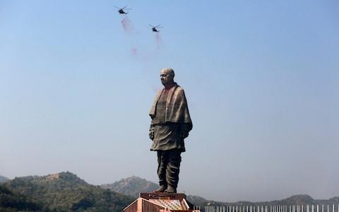 Helicopters shower flower petals on the Statue of Unity during its inauguration - Credit: Ajit Solanki/AP