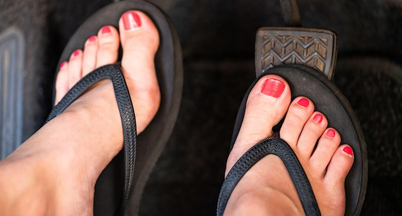 According to Victoria Police, driving with heels, thongs or barefoot was legal. A stock photo of a female driving in thongs with painted toenails.