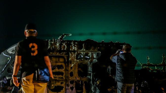 Para petugas memeriksa puing-puing pesawat yang mengalami kecelakaan di ujung landasan pacu 24 di Bandara Internasional Ninoy Aquino, Manila, Filipina (29/3/2020). Akibat insiden kecelakaan ini, delapan orang tewas. (Xinhua/Rouelle Umali)