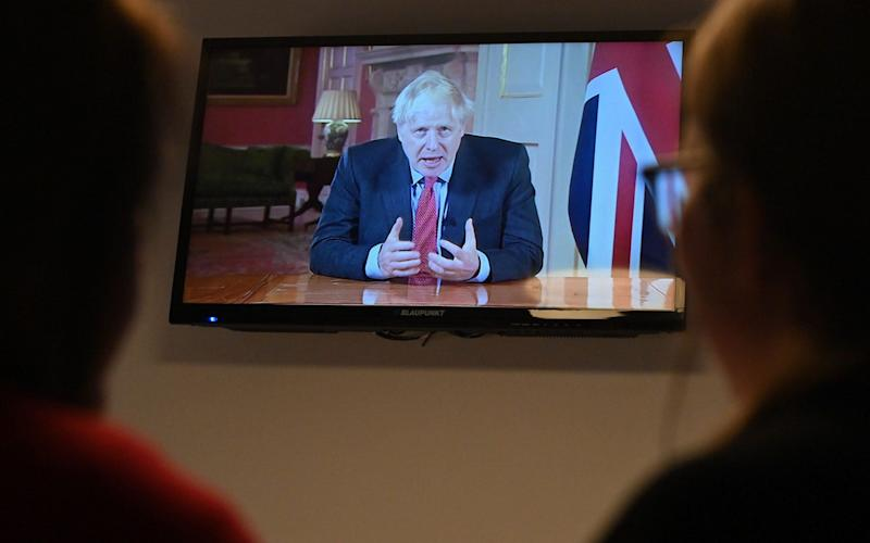 Members of a family watch as Britain's Prime Minister Boris Johnson addresses the nation about the latest updates on the novel coronavirus COVID-19 restrictions, on their television in their home in Liverpool on September 22, 2020. - Britain on Tuesday tightened restrictions to stem a surge of coronavirus cases, ordering pubs to close early and advising people go back to working from home to prevent a second national lockdown - Paul Ellis/AFP