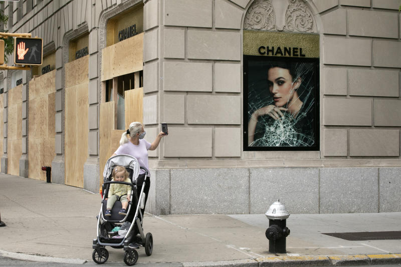 A woman photographs a smashed Chanel store window, Tuesday, June 2, 2020, on Madison Avenue in New York. Protesters broke the window in reaction to the death of George Floyd, a black man who died after being restrained by Minneapolis police officers on May 25. The New York City immortalized in song and scene has been swapped out for the last few months with the virus version. In all the unknowing of what the future holds, there's faith in that other quintessential facet of New York City: that the city will adapt. (AP Photo/Mark Lennihan)