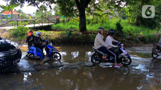 Pengendara motor menerobos lubang yang ada di Jalan Raya Bojonggede, Bogor, Jawa Barat, Sabtu (22/2/2020). Jalan Raya Bojonggede yang berlubang hingga kini belum juga diperbaiki pemerintah setempat membuat kondisi lalu lintas tersendat (merdeka.com/Magang/Muhammad Fayyadh)