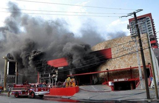 Thick smoke billows from the Casino Royale, in Monterrey, Mexico  as firefighters attack the fire