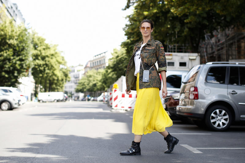 BERLIN, GERMANY - JUNE 16: Actress and TV host Katrin Wrobel wearing a yellow midi skirt by Madeleine, black boots by Shoemates, a camouflage military jacket by Fucking Karma, a white t-shirt by Ohnegleichen and sunglasses by Flair during a street style shooting on June 16, 2020 in Berlin, Germany. (Photo by Streetstyleshooters/Getty Images)