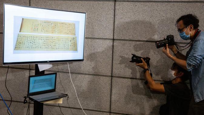 Polisi mengadakan konferensi pers terkait gulungan kaligrafi karya Mao Zedong, yang telah ditemukan, di Hong Kong, 7 Oktober 2020. Pada 10 September 2019, gulungan kaligrafi itu dirampok bersama dengan cap, koin dan karya kaligrafi lainnya yang bernilai total Rp9,5 triliun. (ISAAC LAWRENCE/AFP)
