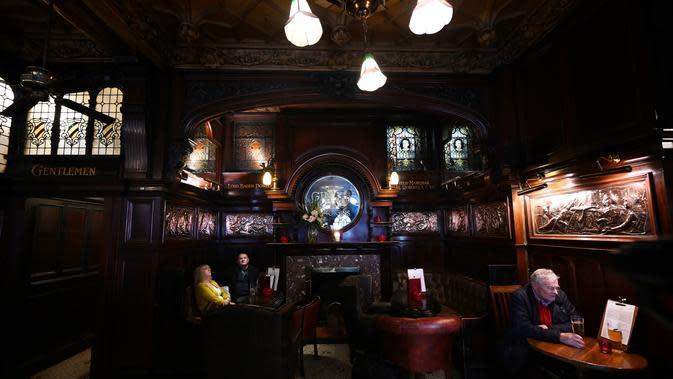 Orang-orang minum di pub Philharmonic Dining Rooms di Liverpool, Inggris pada 11 Februari 2020. Eksterior bagian dalam mulai dari ukiran dinding, kaca patri yang detail, dan perapian mahoni mengelilingi bar yang berbentuk tapal kuda. (Paul ELLIS / AFP)