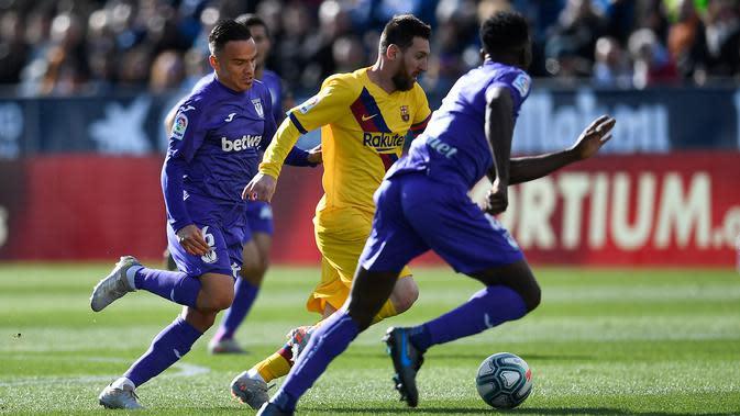 Gelandang Barcelona, Lionel Messi, berusaha melewati gelandang Leganes, Roque Mesa, pada laga La Liga Spanyol di Estadio Municipal Butarque, Leganes, Minggu (23/11). Leganes kalah 1-2 dari Barcelona. (AFP/Pierre-Philippe Marcou)