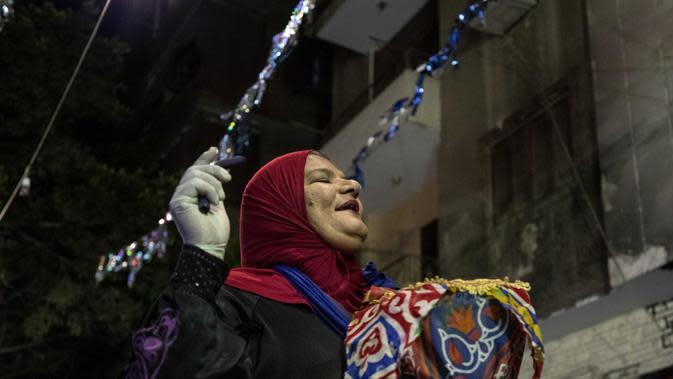Seorang mesaharati Hajja Dalal (46) membangunkan warga untuk sahur saat bulan suci Ramadan di Kairo, Mesir, Rabu (29/4/2020). Untuk membangunkan orang sahur, seorang mesaharati biasanya akan memukul drum yang disebut dengan baza. (AP Photo/Nariman El-Mofty)
