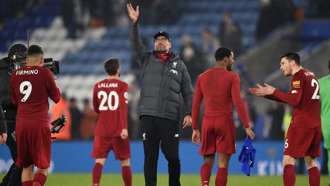 Pelatih Liverpool Jurgen Klopp (tengah) melambaikan tangan kepada para suporter ketika mereka merayakan kemenangan atas Leicester City pada pertandingan Liga Inggris di King Power Stadium, Leicester, Inggris, Kamis (26/12/2019). Liverpool menang 4-0. (Oli SCARFF/AFP)