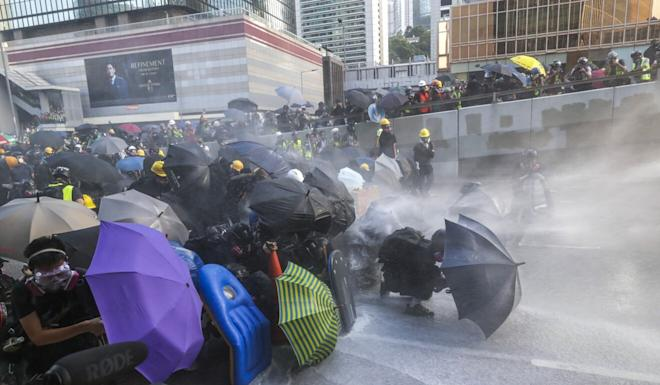 Protesters try to fend off a water cannon blast on September 15 last year. Photo: Edmond So