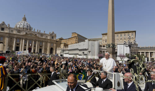 Pope Francis waves at a cheering crowd as he wades through St. Peter's Square at the Vatican, Sunday, March 24, 2013. Pope Francis celebrated his first Palm Sunday Mass in St. Peter's Square, encouraging people to be humble and young at heart, as tens of thousands joyfully waved olive branches and palm fronds. The square overflowed with some 250,000 pilgrims, tourists and Romans eager to join the new pope at the start of solemn Holy Week ceremonies, which lead up to Easter, Christianity's most important day. (AP Photo/Domenico Stinellis)