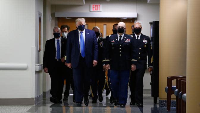 Presiden Amerika Serikat Donald Trump mengenakan masker saat menyusuri lorong dalam kunjungannya ke Pusat Kesehatan Militer Nasional Walter Reed di Bethesda, Maryland, Sabtu (11/7/2020). Trump memakai masker untuk pertama kalinya di depan umum selama pandemi COVID-19. (AP Photo/Patrick Semansky)