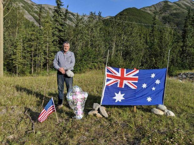 Ed Grennan next to the roadside memorial he created for murdered couple, Lucas Fowler and Chynna Deese.