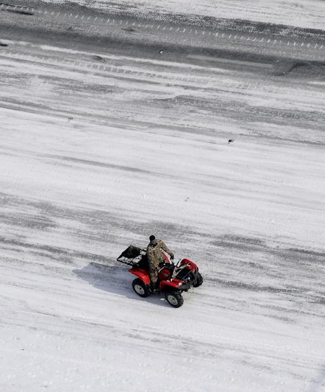In this aerial view, A good Samaritan on a four-wheeler patrols I-75 south at West Paces Ferry Rd. after a winter snow storm Wednesday, Jan. 29, 2014, in Atlanta. Georgia Gov. Nathan Deal said early Wednesday that the National Guard was sending military Humvees onto Atlanta's snarled freeway system in an attempt to move stranded school buses and get food and water to people. Georgia State Patrol troopers headed to schools where children were hunkered down early Wednesday after spending the night there, and transportation crews continued to treat roads and bring gas to motorists, Deal said. (AP Photo/David Tulis)