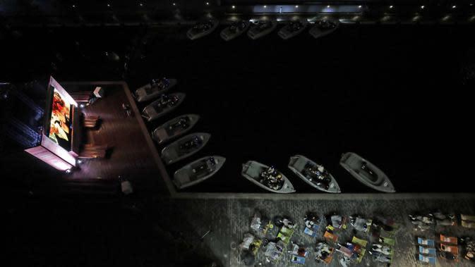 Sejumlah orang duduk di atas perahu dan kursi geladak GoBoat saat menonton film 'Titanic' pada malam pertama pembukaan bioskop apung Openaire di cekungan kanal Paddington, London, Inggris, 2 September 2020. Bioskop luar ruangan disiapkan untuk dijalankan pada bulan September. (AP Photo/Matt Dunh