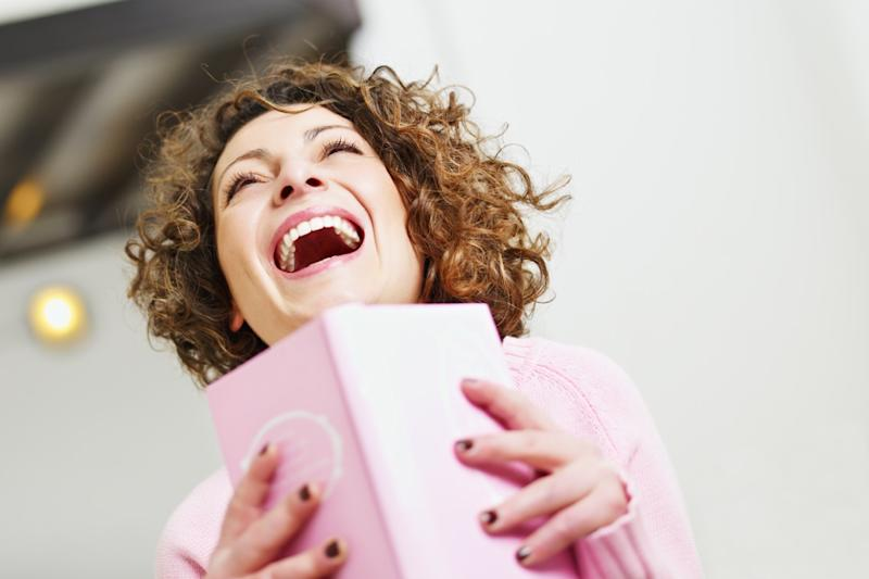 woman laughing while reading a book, stay at home mom