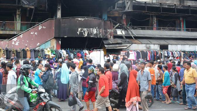 Para pedagang menjajakan dagangannya di depan gedung Pasar Senen pasca kebakaran, Jakarta, Minggu (22/1). Karena akhir pekan pengunjung justru tumpah ruah di Pasar Senen untuk memilah baju bekas. (Liputan6.com/Helmi Affandi)