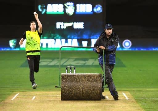Melbourne Cricket Ground (MCG) curator Matt Page rolls the pitch as Australian bowler Jason Behrendorff practises during the innings break of the Australia v India T20 international