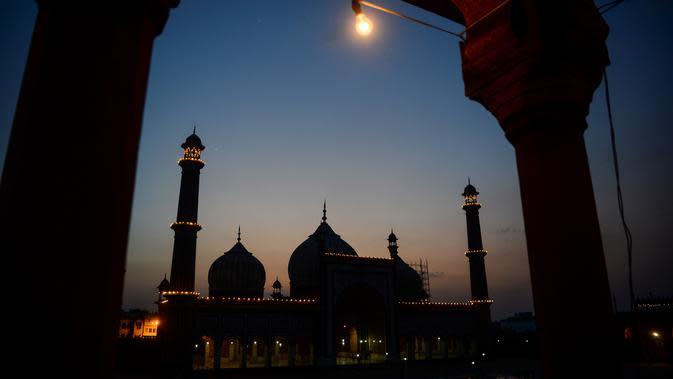 Masjid Jama diterangi cahaya pada bulan suci Ramadan di bawah penerapan lockdown untuk menekan penyebaran virus corona di New Delhi , 25 April 2020. Masjid terbesar di India itu selalu ramai dipenuhi orang-orang saat datangnya Ramadan namun, kini terlihat sepi imbas Covid-19. (Sajjad HUSSAIN/AFP)