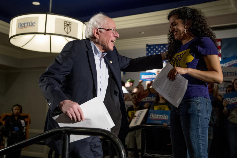 Democratic presidential candidate Sen. Bernie Sanders, I-Vt., left, is welcomed to the stage by Sunrise Movement co-founder Varshini Prakash, right, at a climate rally with the Sunrise Movement at The Graduate Hotel, Sunday, Jan. 12, 2020, in Iowa City, Iowa. (AP Photo/Andrew Harnik)