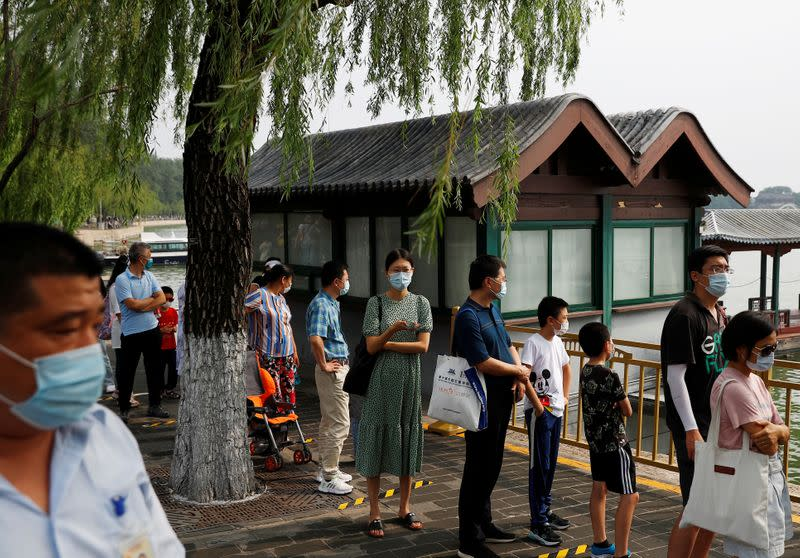 People wearing protective masks line up in the park at Summer Palace on a public holiday, after a new outbreak of the coronavirus disease (COVID-19), in Beijing