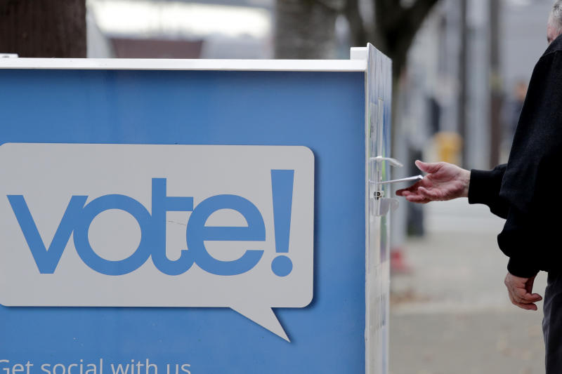 A voter drops a ballot into a ballot drop box Monday, Nov. 4, 2019, in Seattle. Voters in Washington state have a crowded ballot to fill out for this week's election, with a referendum on affirmative action and an initiative on the price of car tabs among the things they are being asked to decide. (AP Photo/Elaine Thompson)