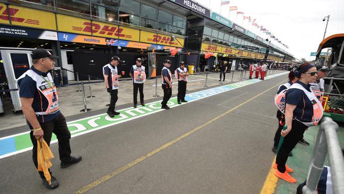 Tim berdiri di luar lapangan sebelum Formula 1 Australia Grand Prix dibatalkan di Melbourne, Jumat (13/3/2020). Pembatalan F1 Australia menjadi lanjutan dari keputusan Mclaren yang sudah menyatakan mundur dari balapan. (Peter PARKS/AFP)