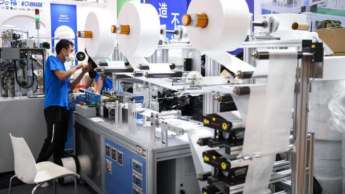 Seorang staf menyesuaikan mesin pembuat masker di area pameran dalam ajang Guangzhou Fair ke-28 di Guangzhou, Provinsi Guangdong, China selatan (28/8/2020). Ajang yang akan berlangsung selama empat hari tersebut dibuka di Guangzhou pada Jumat (28/8). (Xinhua/Deng Hua)