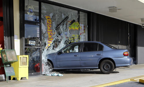"In this July 24, 2013, photo, a stunt car crashes into a storefront during the taping of an episode of ""Burn Notice"" in Miami. The cable spy drama is coming to an end after seven seasons with a big finale Thursday, Sept. 12, 2013. (AP Photo/Alan Diaz)"