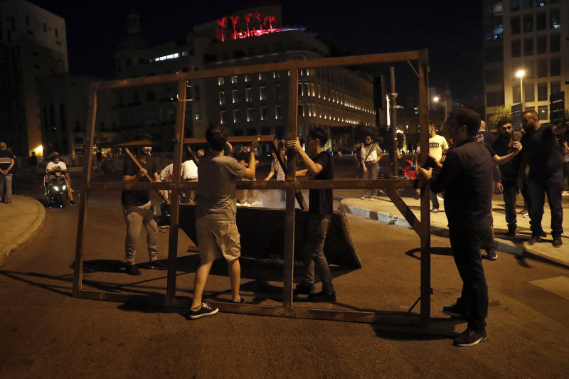 Anti-government protesters block a road during a protest against the political leadership they blame for the economic and financial crisis, in Beirut, Lebanon, Thursday, June 11, 2020. (AP Photo / Hussein Malla)
