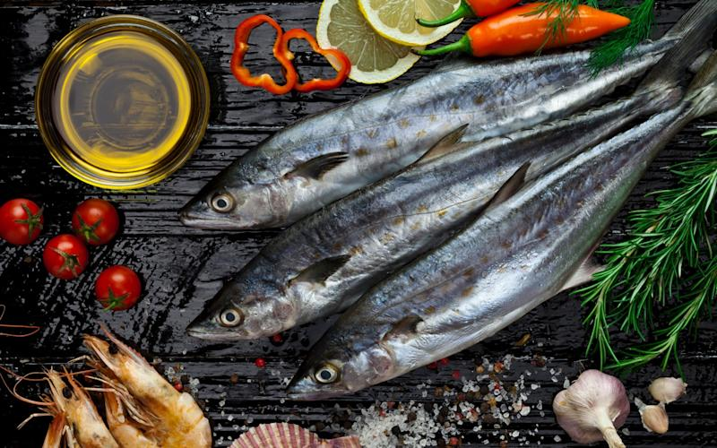 Three raw mackerel fish shot directly above on dark table with seafood and some ingredients for cooking. - E+/fcafotodigital