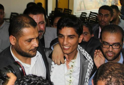Arab Idol winner Palestinian Mohammed Assaf, center, arrives to the Rafah crossing point on the border between Egypt and southern Gaza Strip, Tuesday, June 25, 2013. Huge crowds of Gazans gave a gleeful welcome Tuesday to the first Palestinian winner of the Arab Idol talent contest, thronging the territory's border crossing with Egypt and the singer's home in hopes of embracing him, but internal politics surfaced quickly. Assaf's victory in the popular contest Saturday sparked huge celebrations in the West Bank and Gaza, giving Palestinians a sense of pride. (AP Photo/Khaled Omar, Pool)
