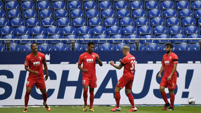 Pemain Augsburg, Noah Saranren Bazee, melakukan selebrasi usai membobol gawang Schalke 04 pada laga Bundesliga di Veltins-Arena, Minggu (24/5/2020). Augsburg menang dengan skor 3-0 atas Schalke 04. (AP/Martin Meissner)